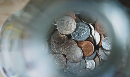 Peníze ve sklenici představující pomyslný veřejný dluh Česka.